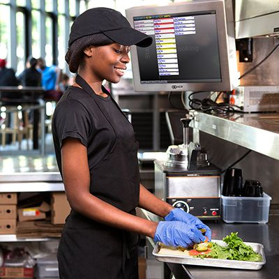 woman using NCR kitchen production system in a restaurant