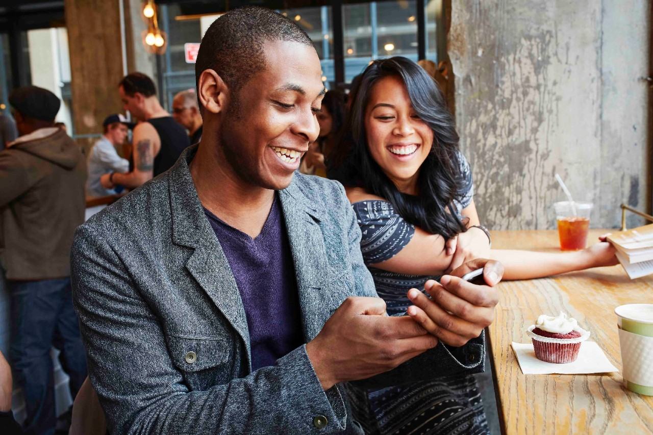 Couple of friends laughing at phone at a table in cafe