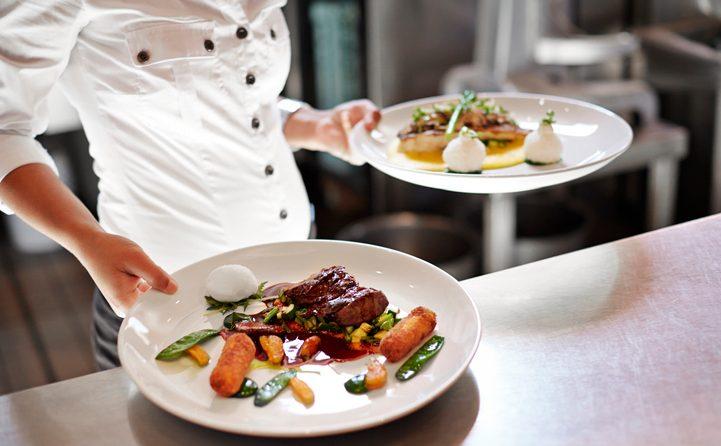 Waiter picking up dishes in kitchen at restaurant