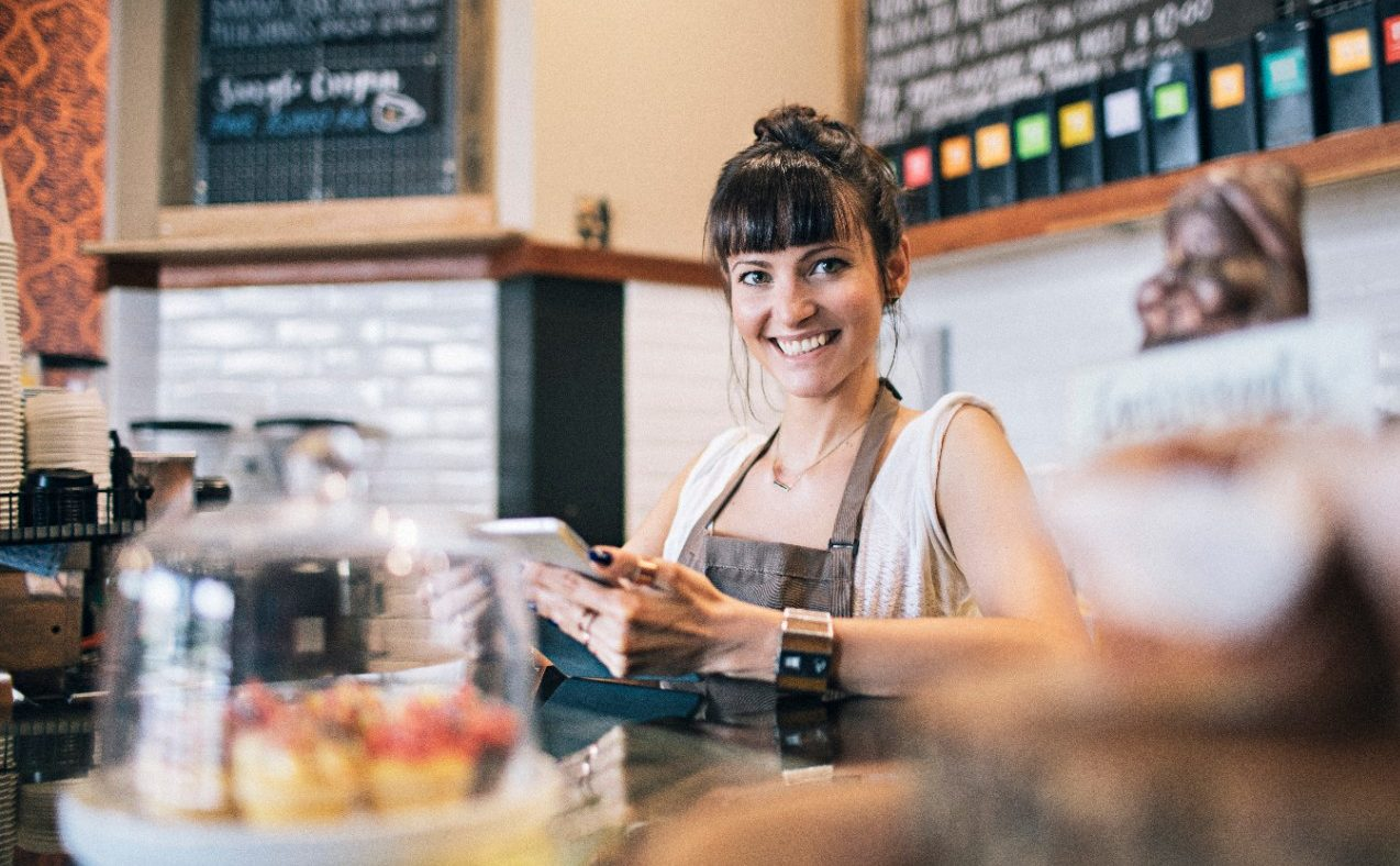 Proud coffee shop owner using her digital tablet writing the ingredients she needs.