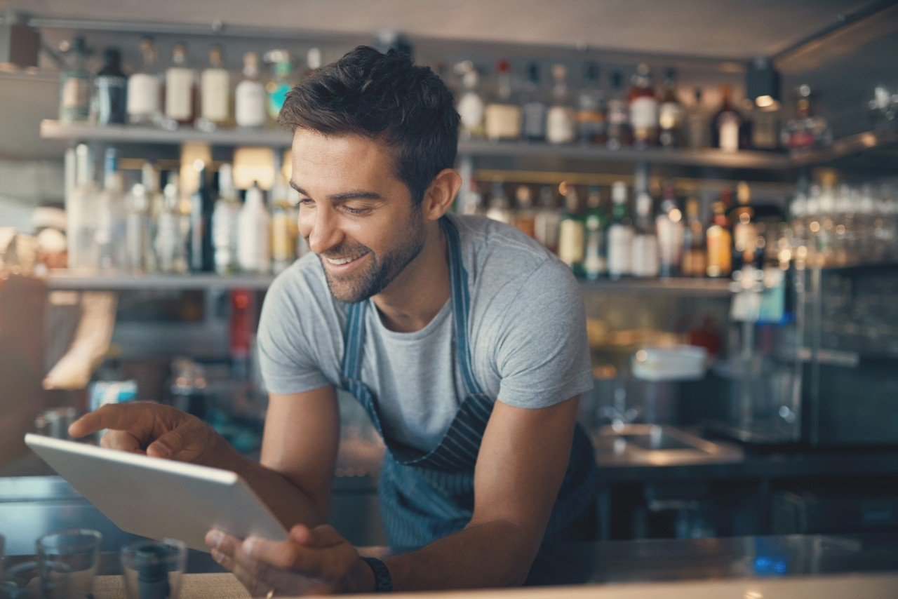 Shot of a young man using a digital tablet while working behind a bar counter