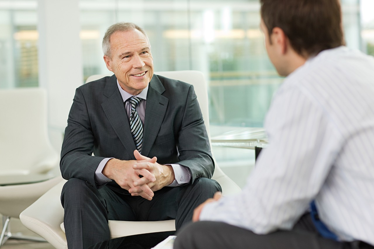 payments two men talking in office meeting