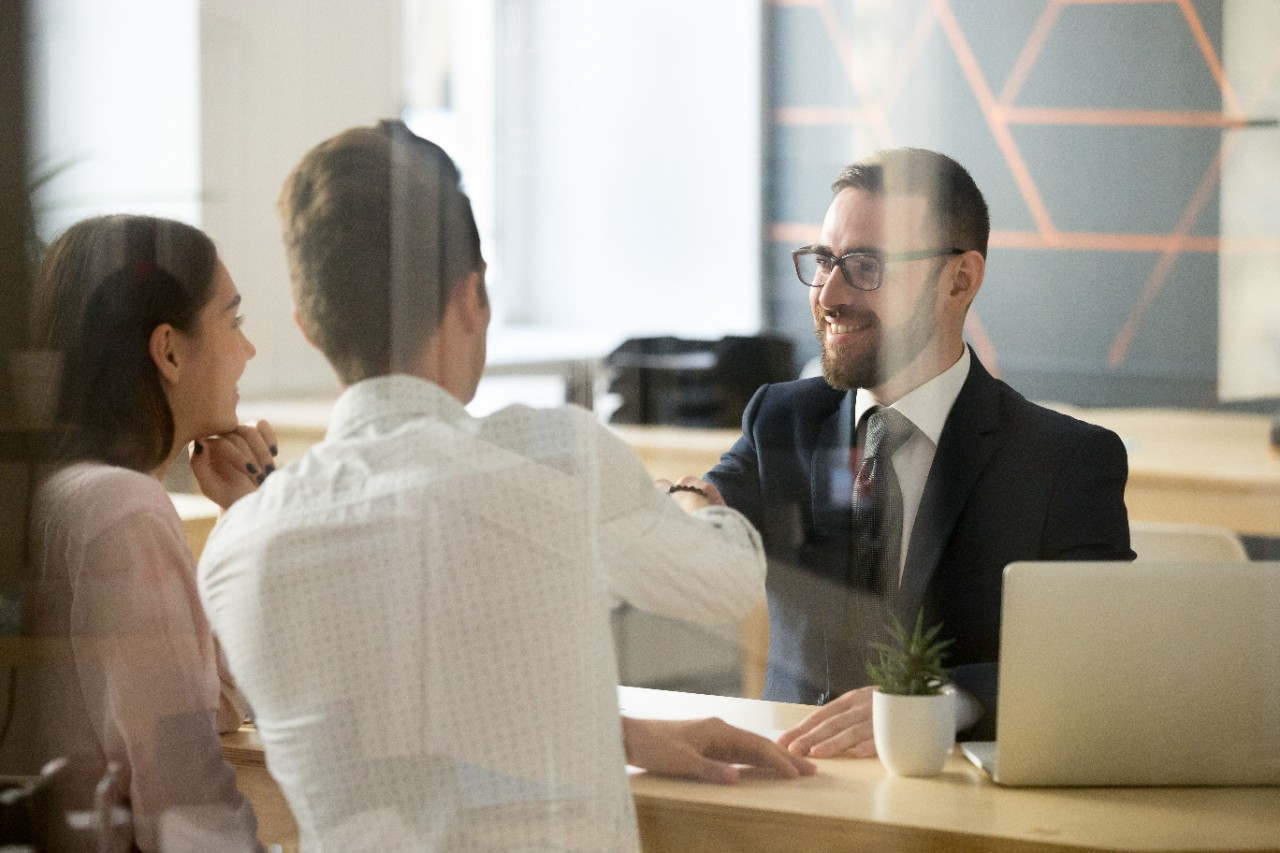Smiling male realtor or banker or broker shaking hand of excited buyers couple, negotiating about first house purchase or taking loan, insurance agent welcoming clients with handshake at consultation meeting