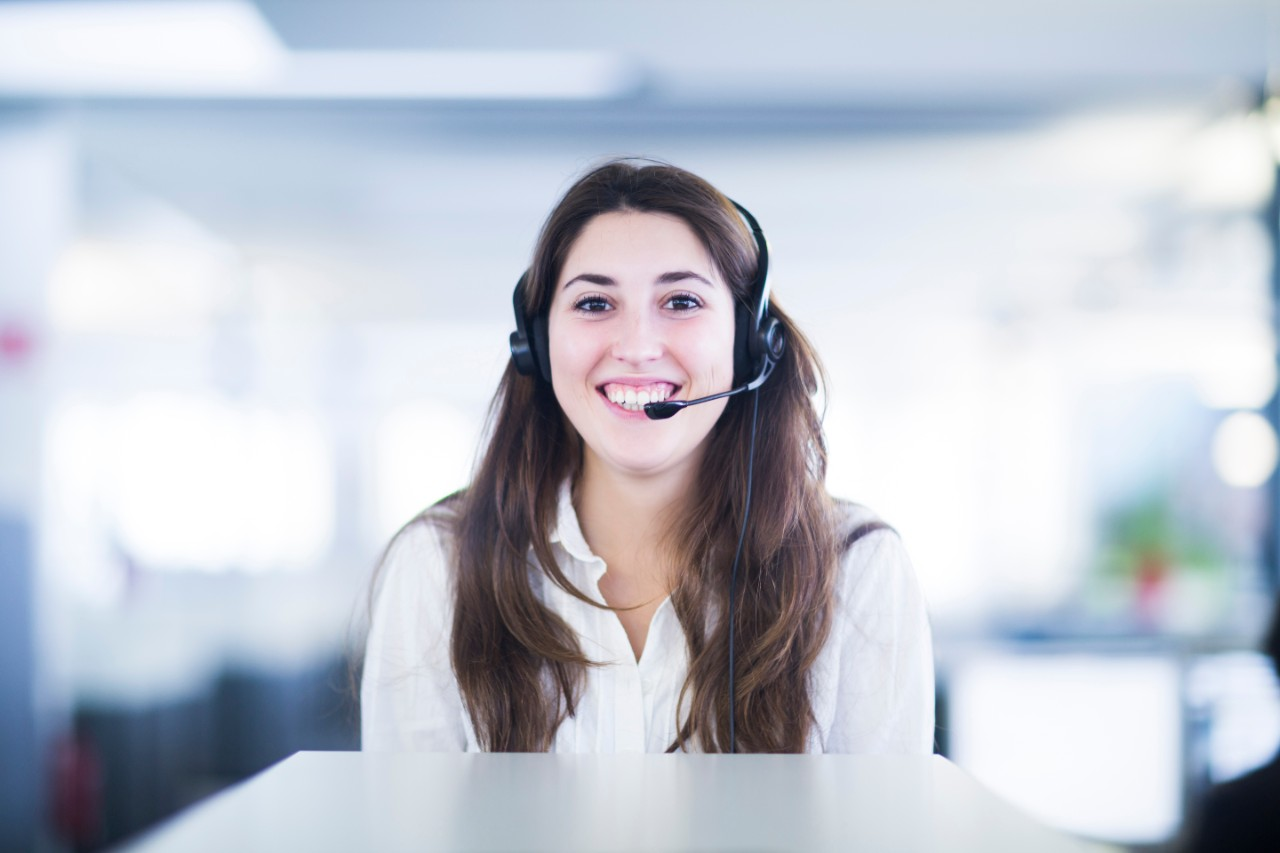 young female woman girl smiling with headset on in office digital connected services