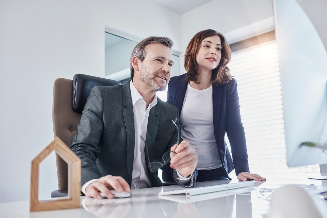 Deutschland, Wiesbaden, Business, Büro, Businessmann und Geschäftsfrau schauen in einen Computer, Architekturmodell, Immobilie