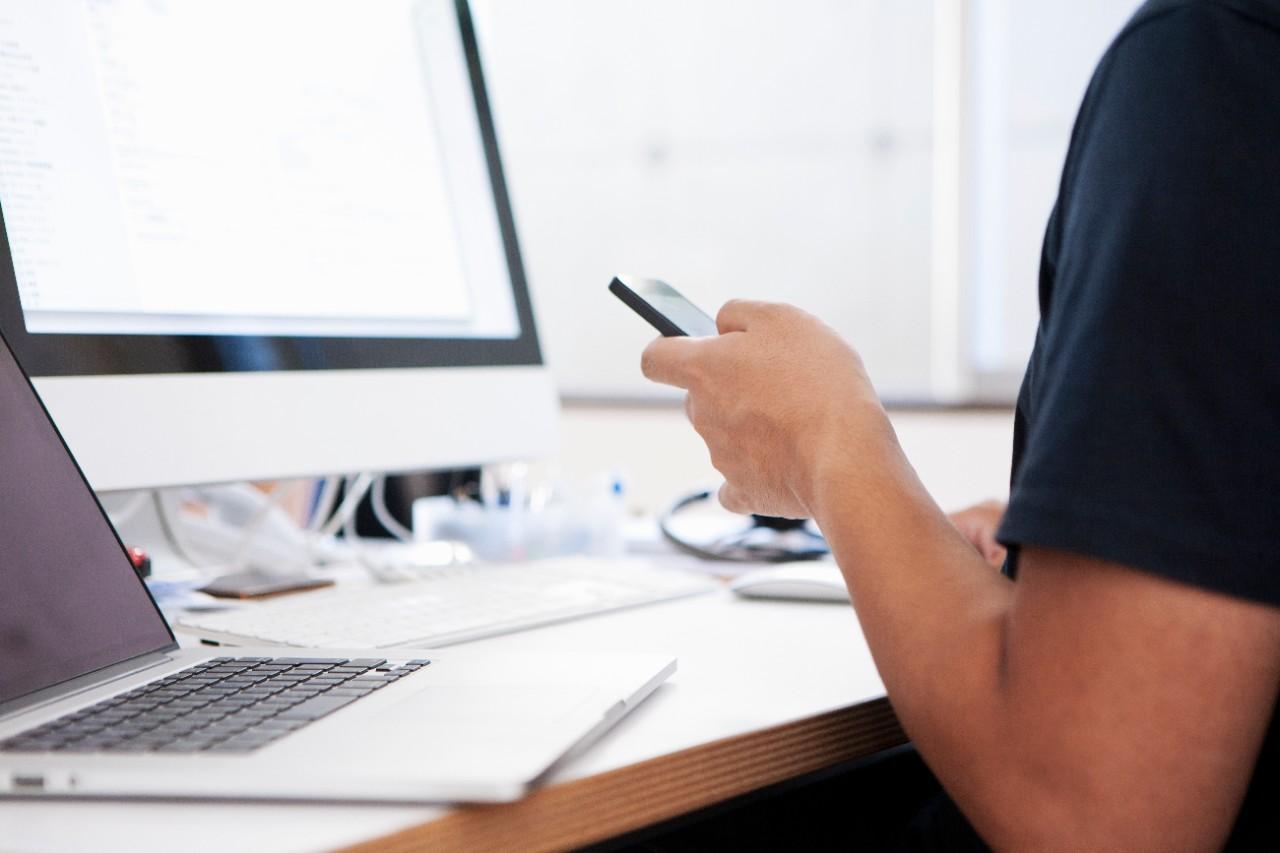 A hand of a web designer holds a smart phone at design studio.