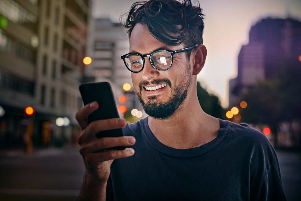 Male man smiling outside in city looking at mobile phone