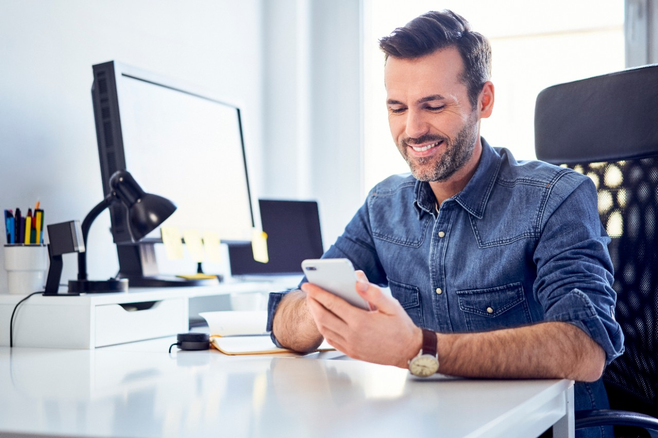Man male smiling at desk in office with his computer and mobile phone for connected services and management