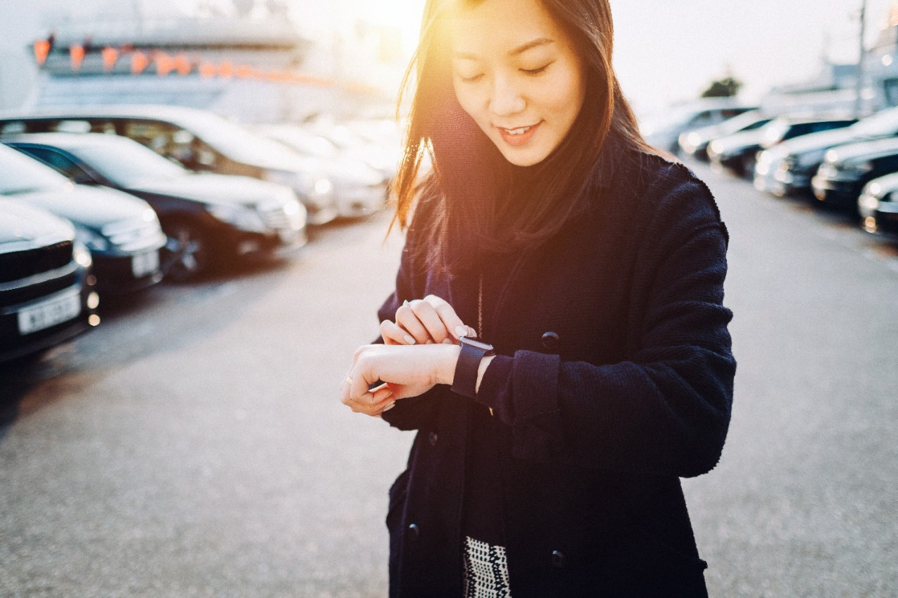 Beautiful young Asian woman checking time on smartwatch in city, in front of cars in outdoor carpark at sunset