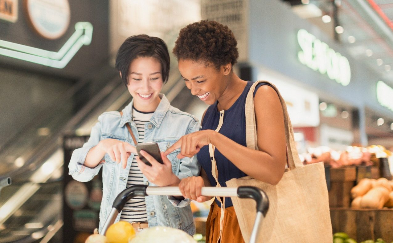 Two females point at phone screen smiling in grocery store