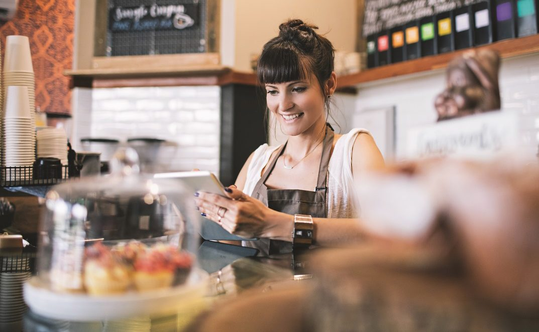 Coffee shop owner posting the new cafeteria breakfast deals on the social media using her digital tablet.