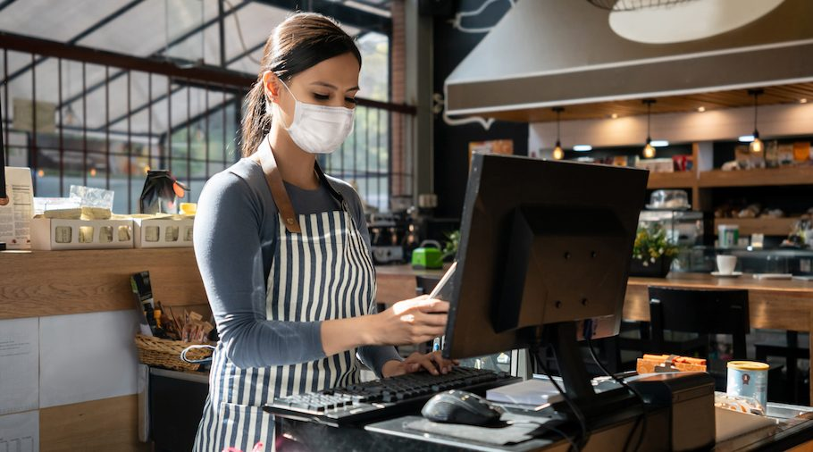 Portrait of a waitress working at a restaurant wearing a facemask and placing the order in the computer – pandemic lifestyle concepts