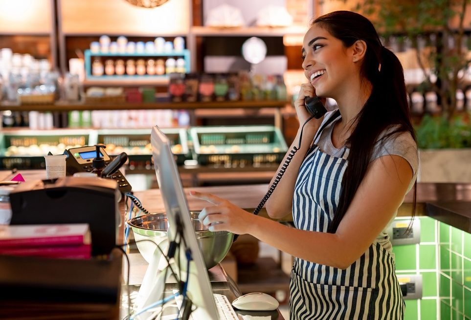 Friendly waitress taking a take out order on phone while adding it to the system smiling very happy