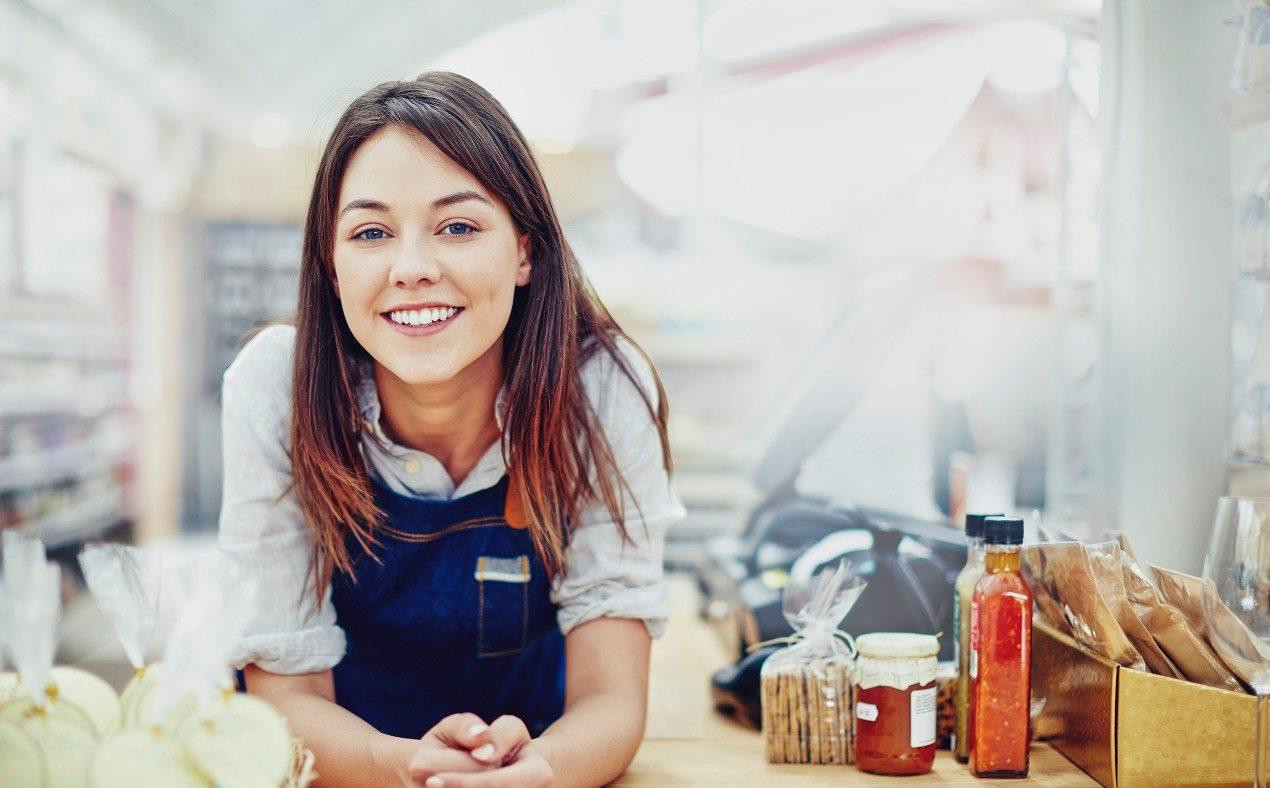 Portrait of confident deli owner leaning on checkout counter. Happy young saleswoman is in store. She is wearing denim overalls.