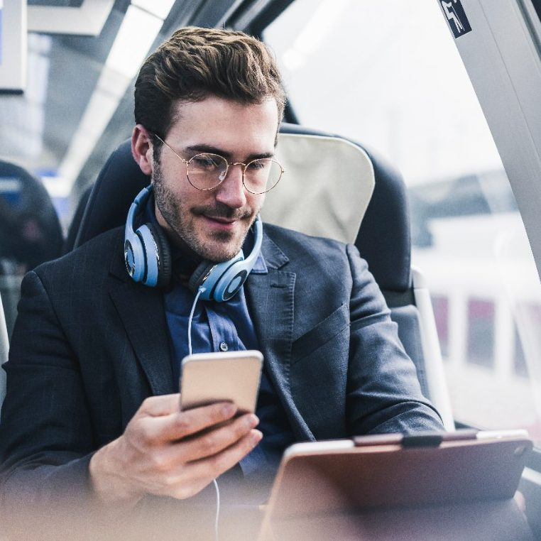 male man on train or bus using his phone and tablet computer to do work and professional services