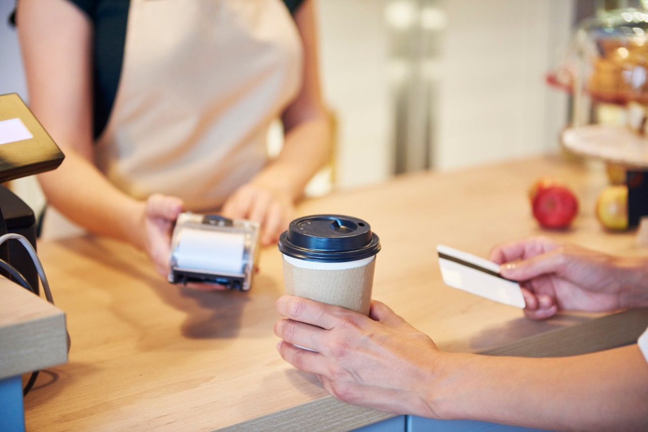Close-up of customer paying by credit card in a cafe