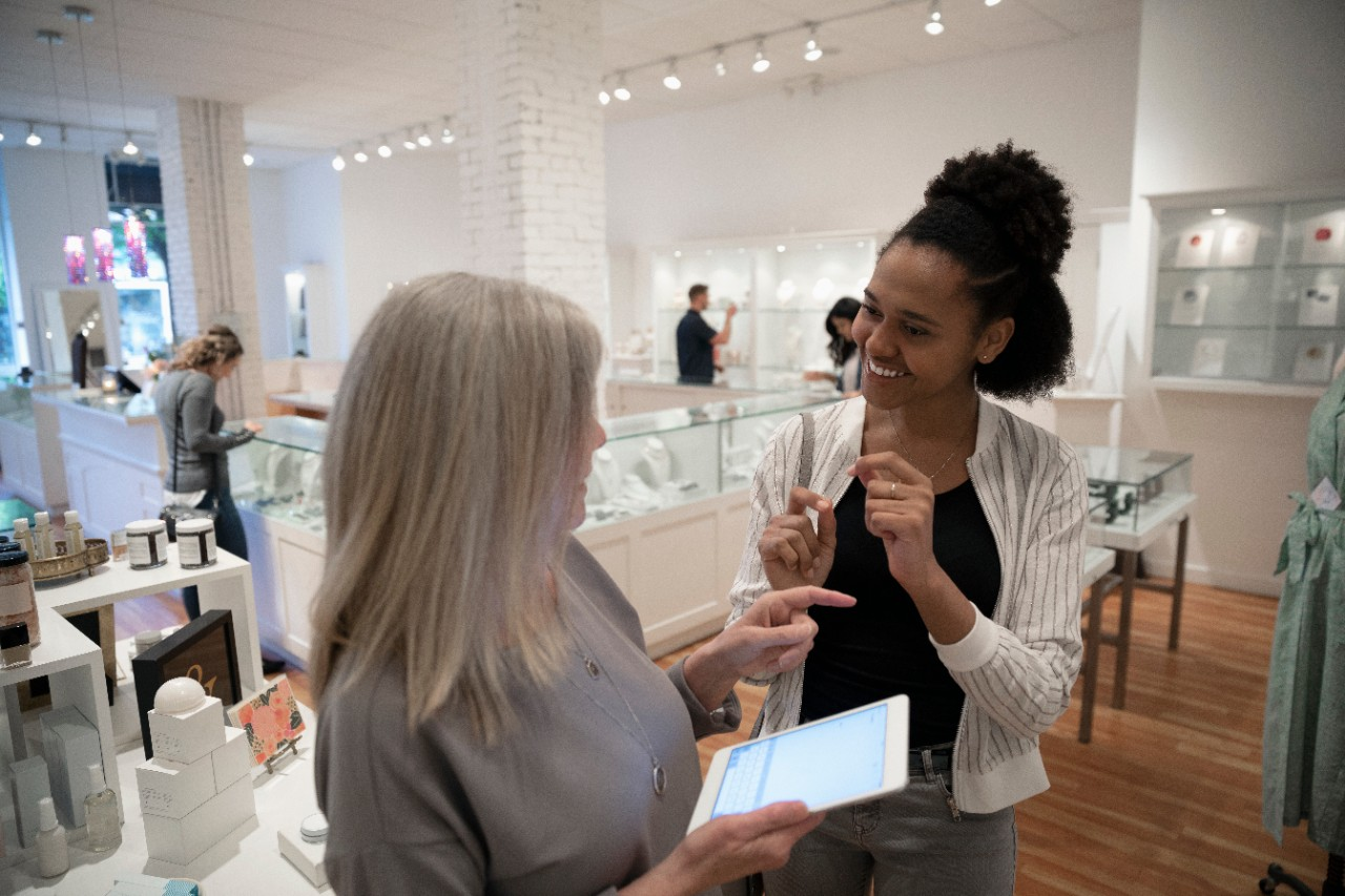 Tablet POS system, female shopper, and female employee in boutique