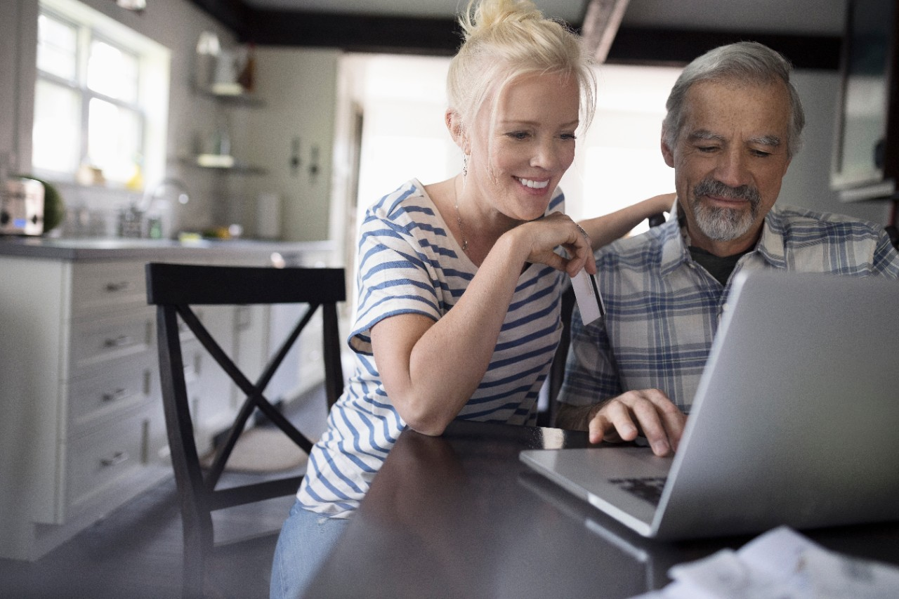 Couple online shopping on laptop holding credit card at home and smiling