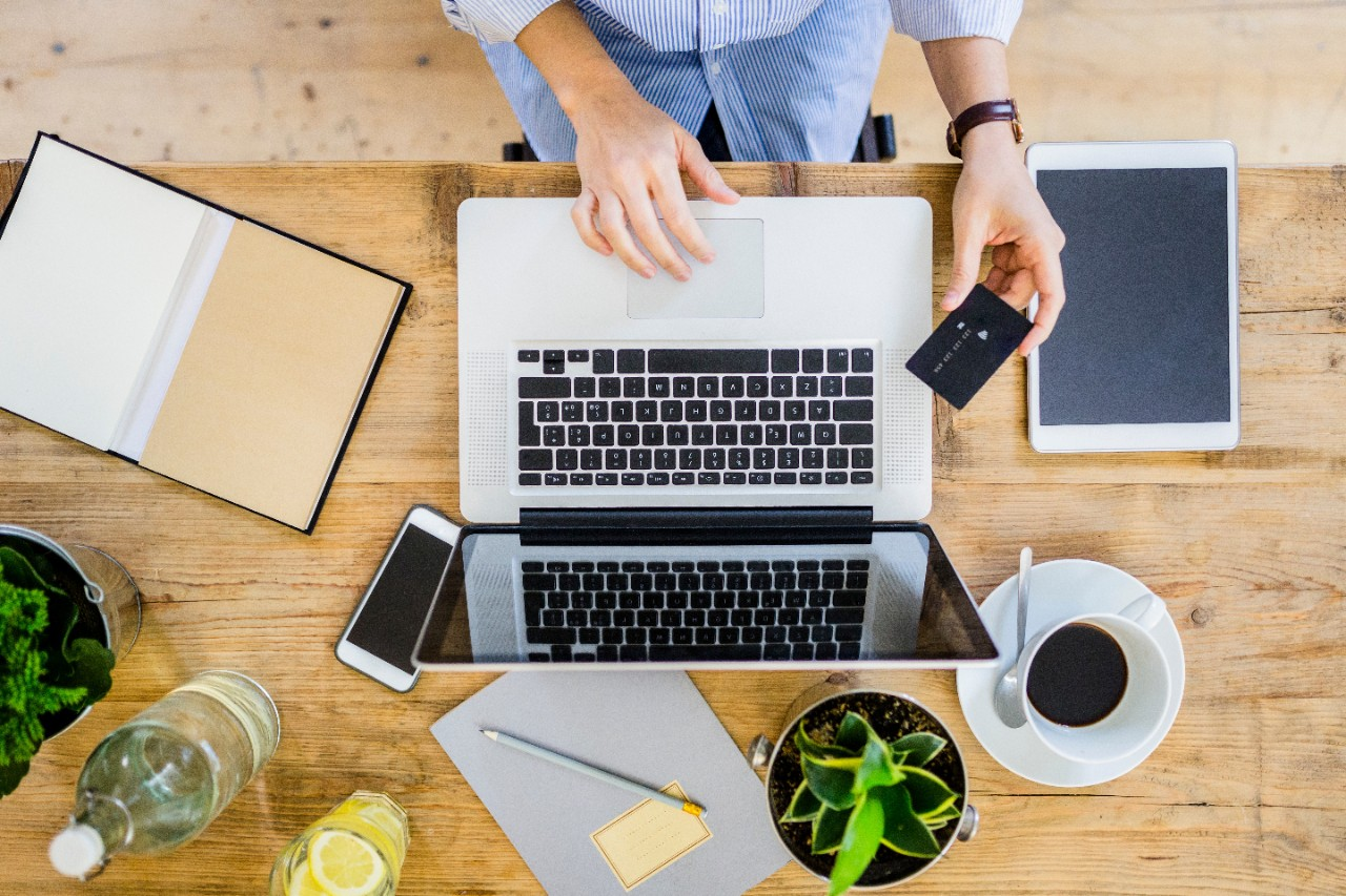 Online shopping aerial desk view with credit card, phone, laptop, and tablet