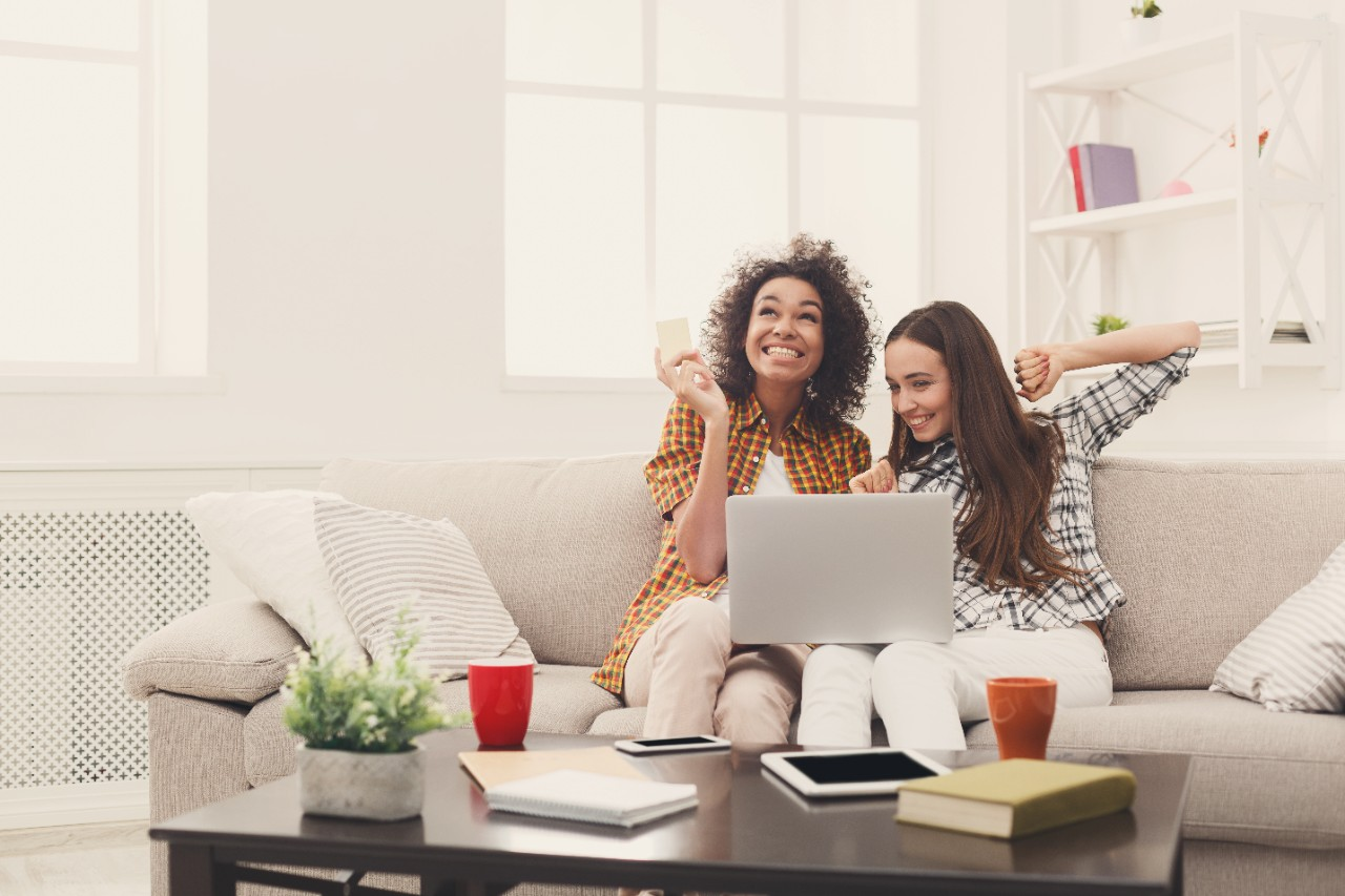 two young female women girls smiling on the couch shopping online holding credit card