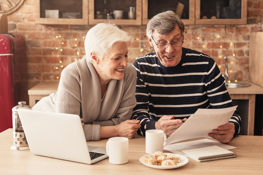 Smiling Senior Couple Reading Health Insurance Policy Contract In Kitchen Together, Discussing Terms
