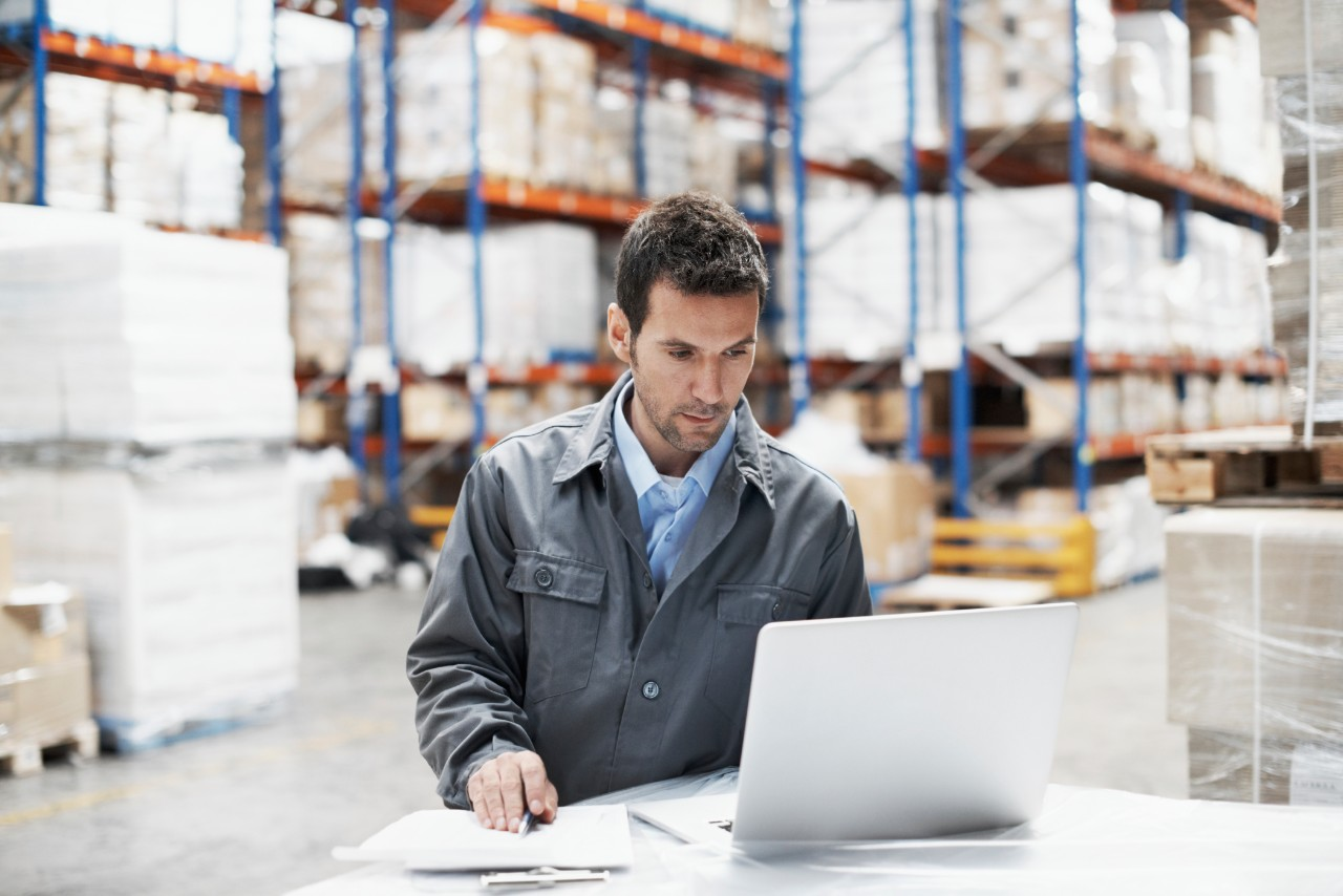 A young man using his laptop and checking his notes while working in a warehouse