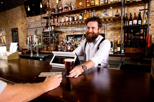 Man serves alcohol to another man