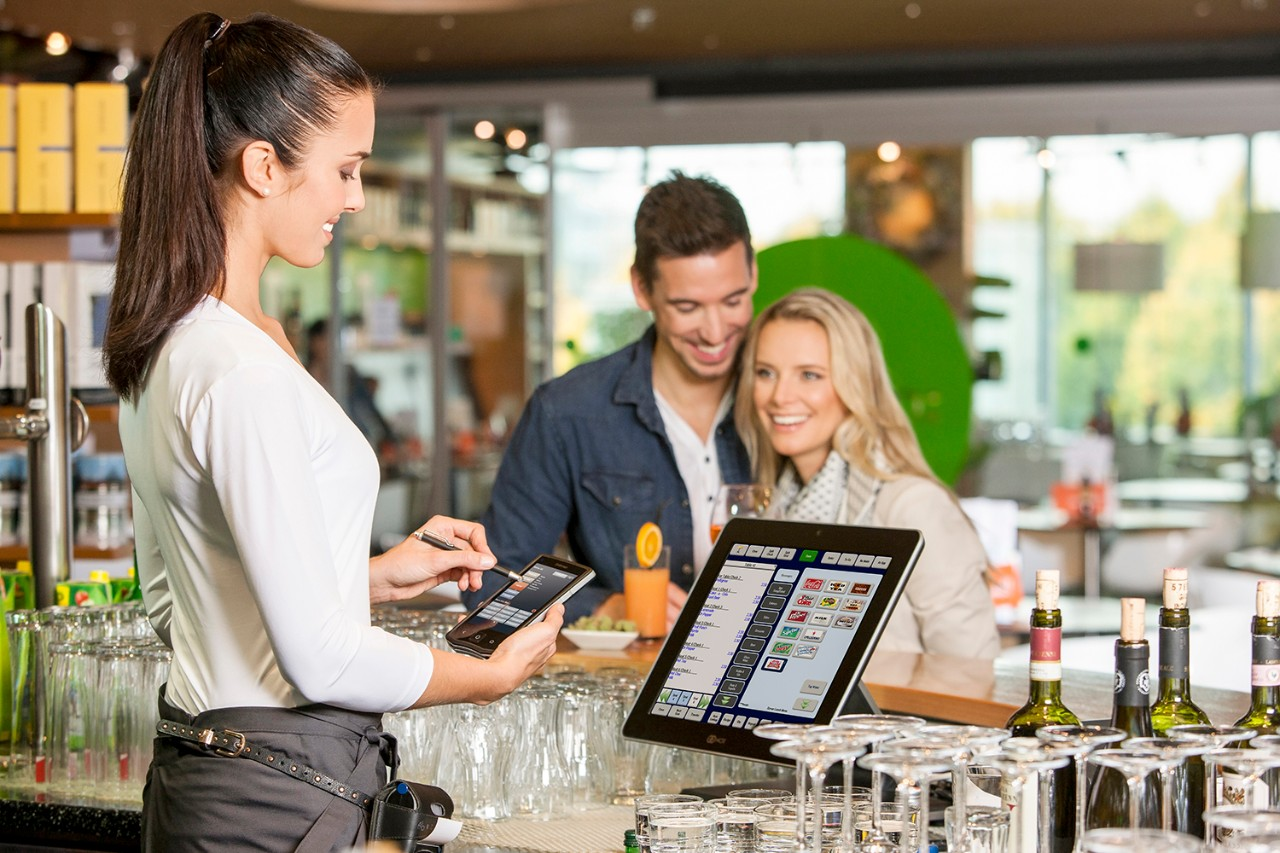 Widescreen - Female employee taking a couple's drink order on a mobile POS with view of countertop POS at the bar