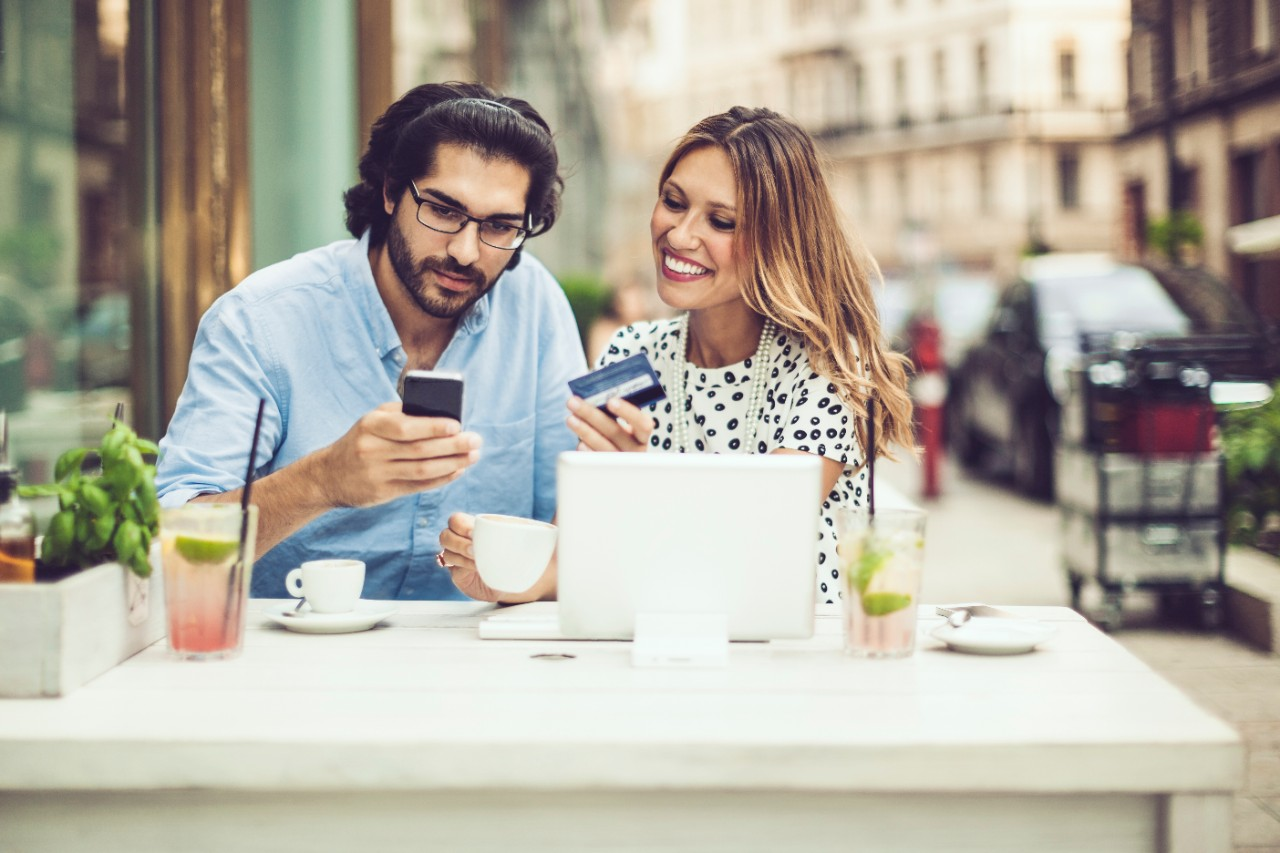 Young couple is having a coffee break and mobile shopping with credit card, phone, and laptop