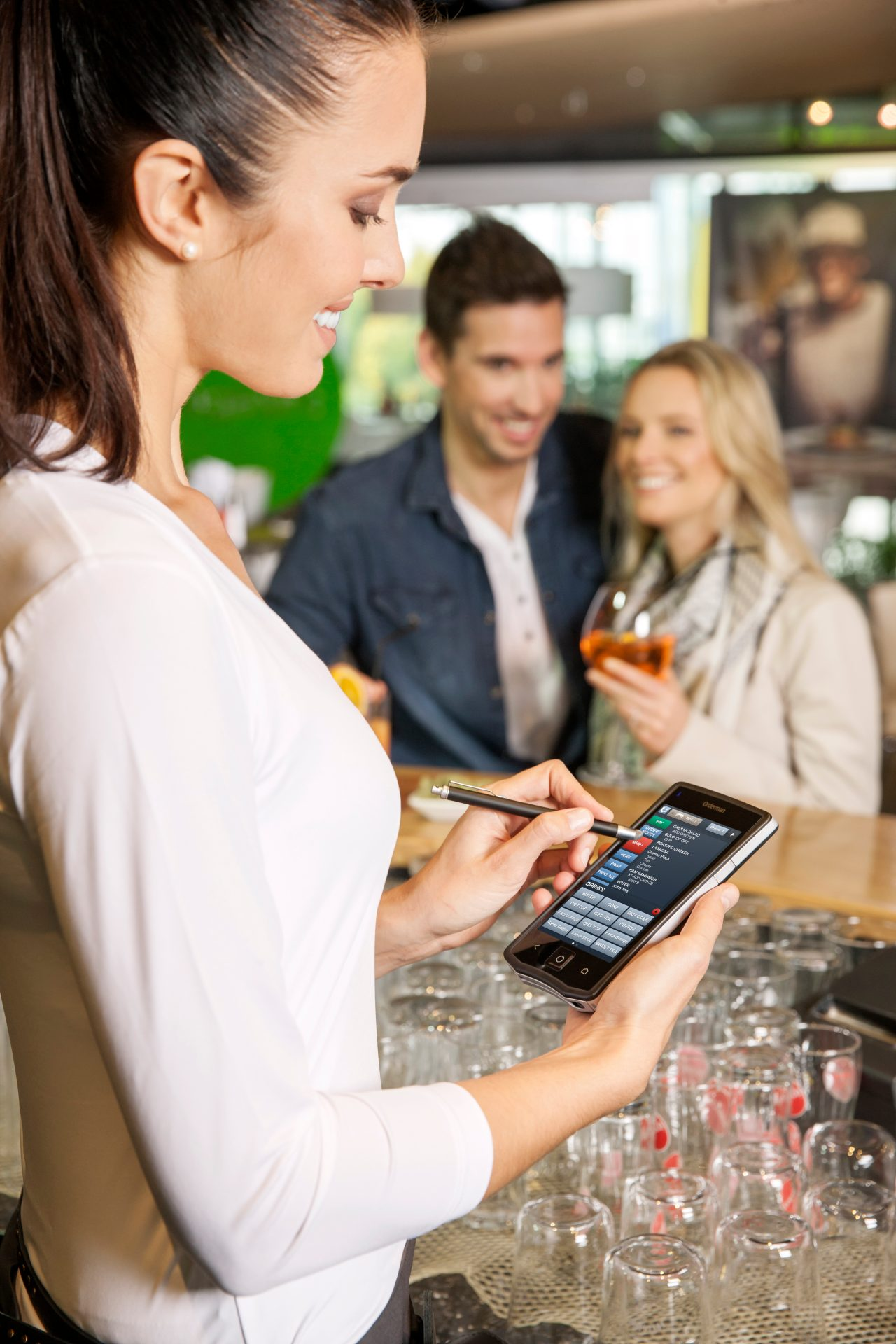 Female employee taking a couple's drink order on a mobile POS at the bar