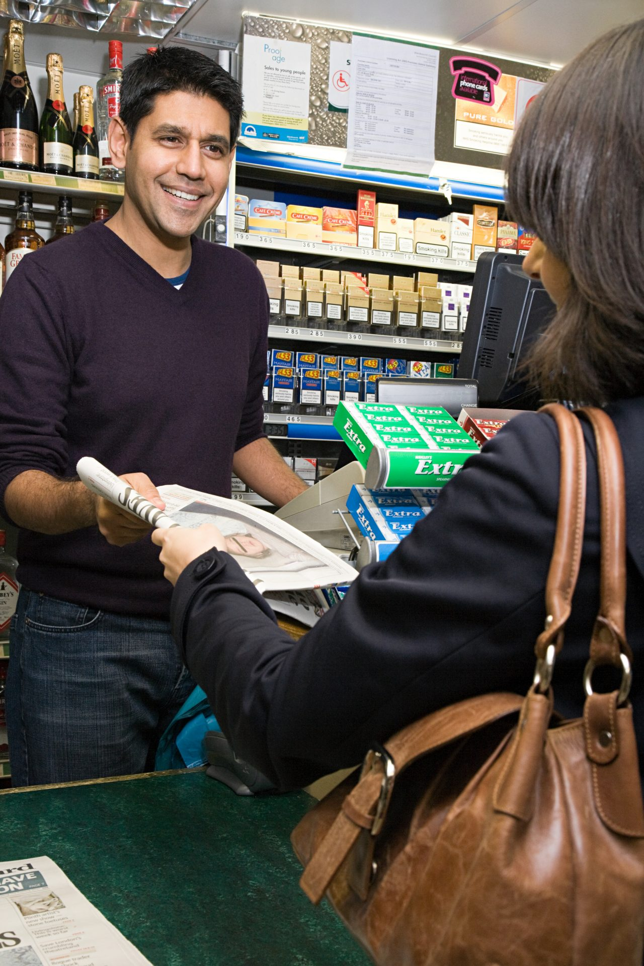 Woman buying newspaper inside gas station