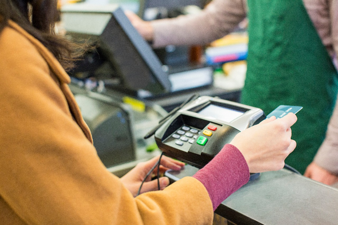 Woman swiping card at grocery store checkout - USA, Oregon, Portland
