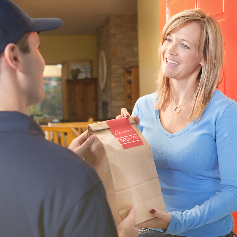 A delivery service man delivering a take-out food bag to a woman customer at her home front door. The cheerful dinner delivery person wears a polo shirt and cap uniform and greets the smiling housewife. The happy female homeowner receives the convenient fast food meal at her residential building entrance.