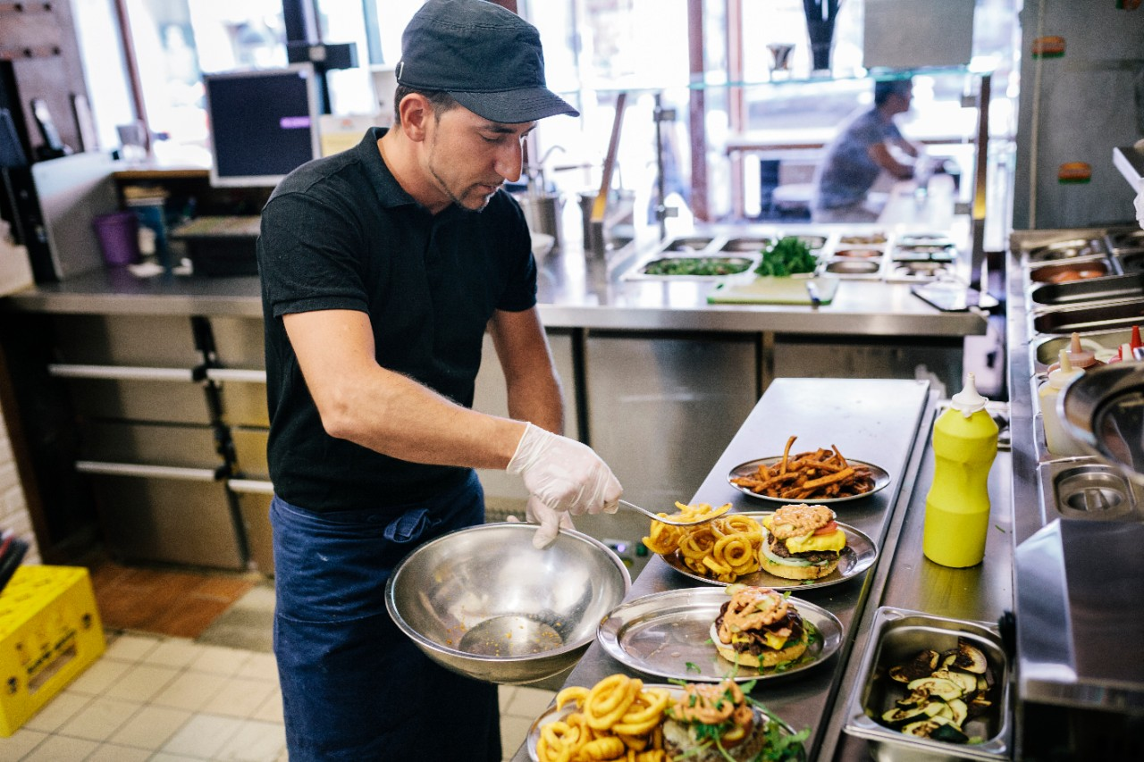 A chef preparing food for his customers in a trendy, gourmet burger restaurant.