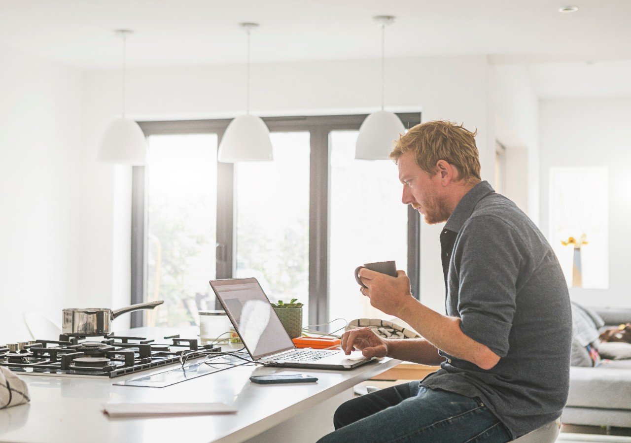 man male sitting at kitchen bar with coffee searching online on laptop