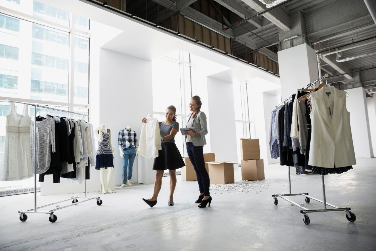 Two women comparing inventory in clothing warehouse