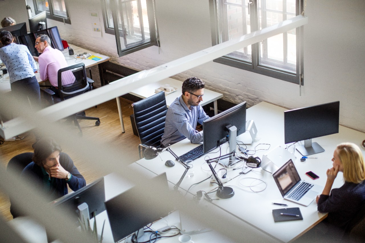 High angle view of office workers using computers, phones, and tablets while sitting at desks in creative office