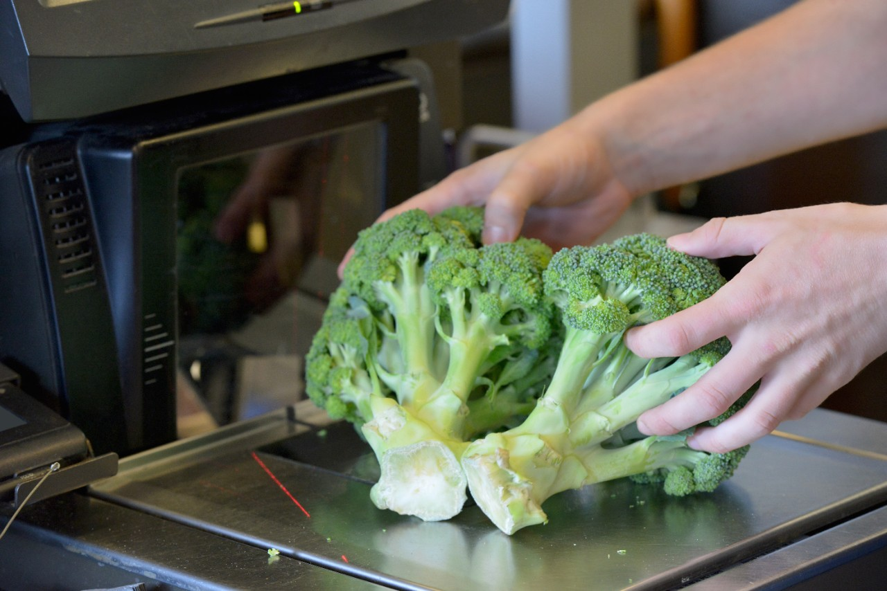 Person scanning broccoli at a grocery store in self checkout
