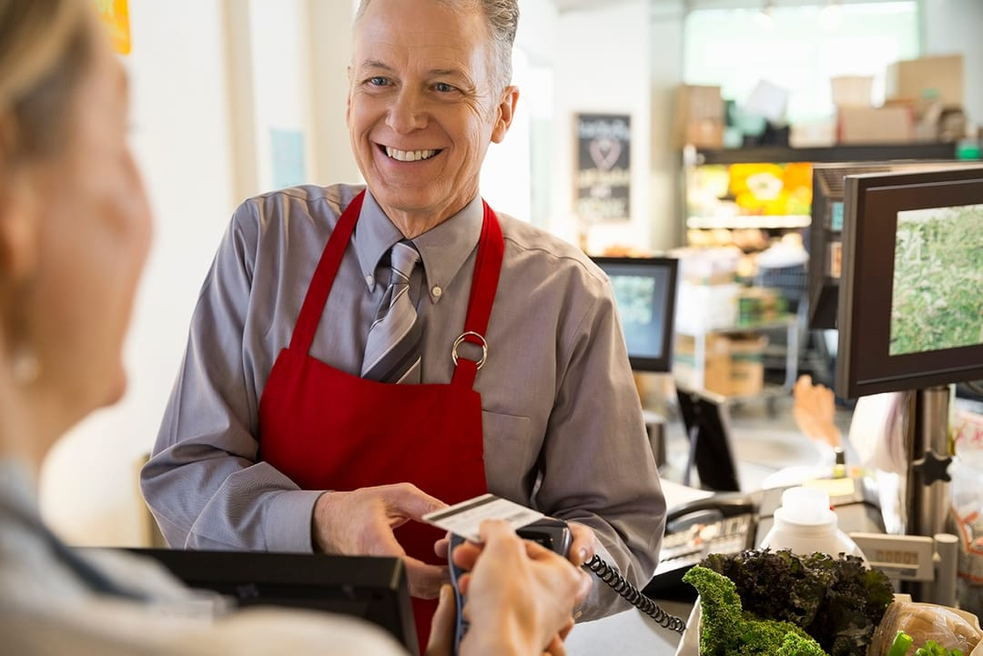Smiling Man in the Store with Credit Card
