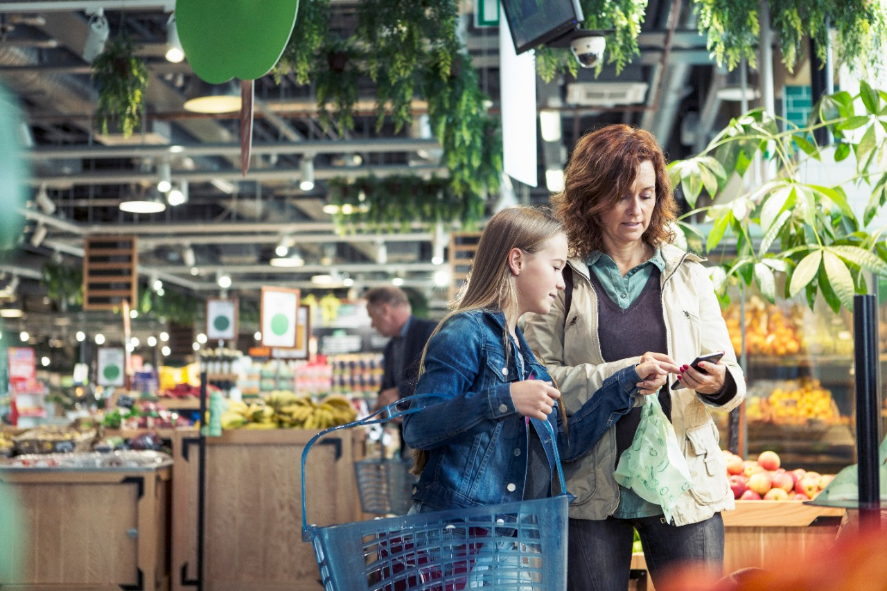 Young daughter and mom looking at smart phone in grocery store