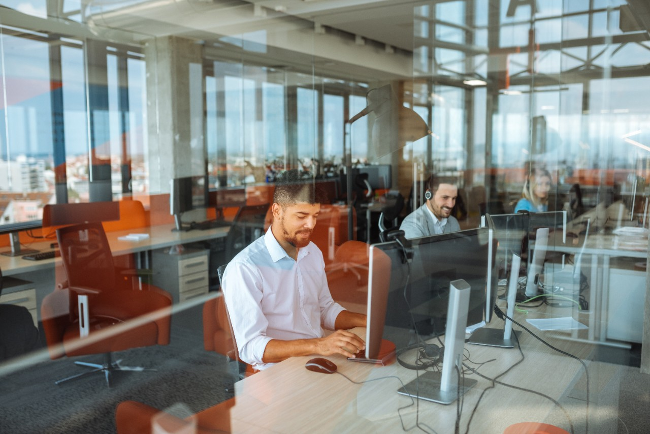 teams of professionals working and smiling at desk in city