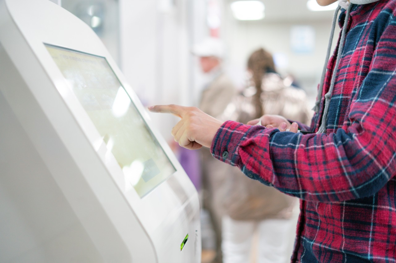close up person using touch screen panel in post office to recieve a package
