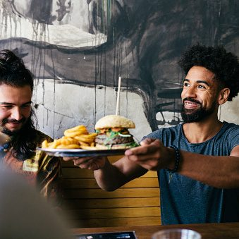 A customer smiling as he receives his food at a trendy burger restaurant.