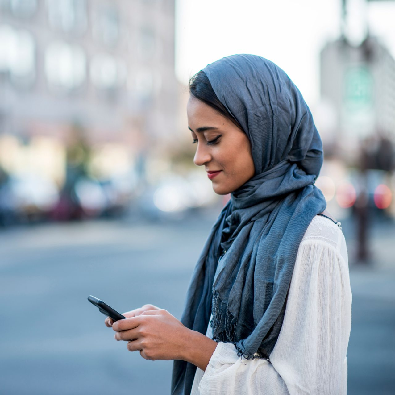 Woman smiling down at phone outside