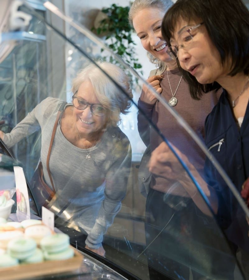 People looking through a display case at desserts